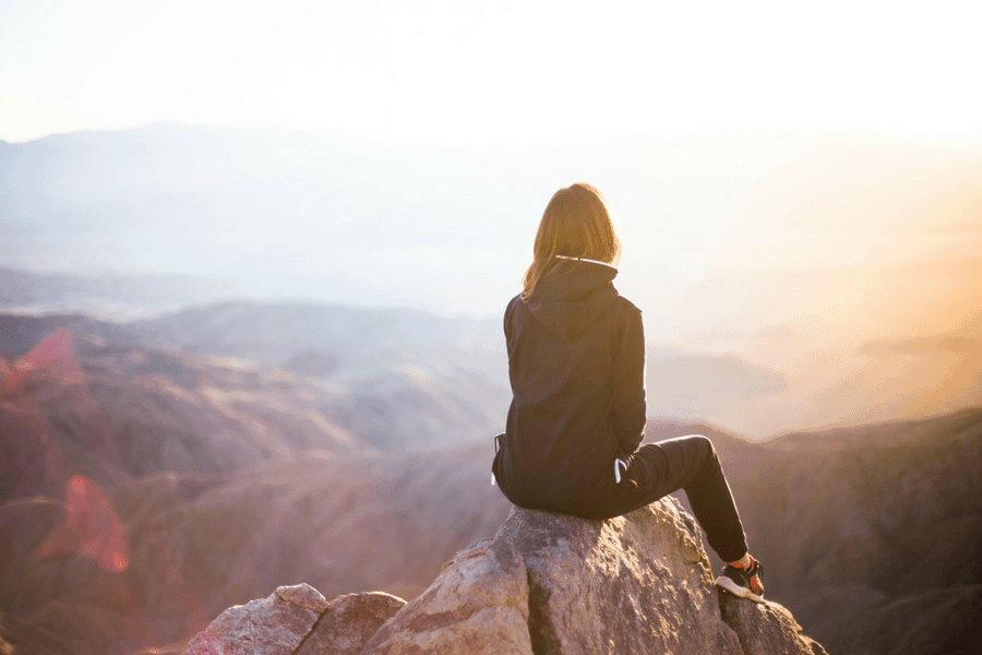 woman sitting on a mountain accomplished goal